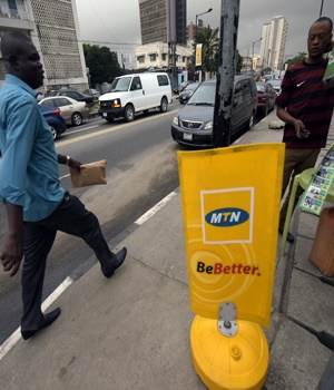 A man walks past a MTN notice board in Lagos, on October 27, 2015.  Nigeria's telecommunications regulator has fined South African mobile giant MTN $5.2 billion for missing a deadline to disconnect unregistered SIM cards, the company announced on Monday. The penalty saw shares in Africa's largest telecommunications company crash more than 12 percent to 167 rand on the Johannesburg Stock Exchange, the biggest fall the firm has suffered in a day since November 1998. AFP PHOTO/PIUS UTOMI EKPEI